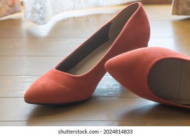 Red women highheel shoes on wooden floor