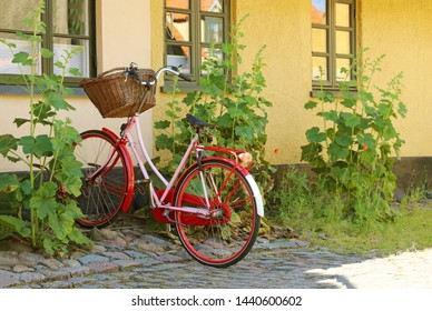 Red women's bicycle with a basket. Bike are parked in a bicycle rack. Dragor, Copenhagen, Denmark.