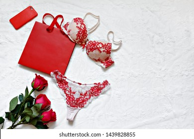 Red women's lingerie and red roses on white surface. Flat lay. Copy space. Gift Concept. Romantic evening.