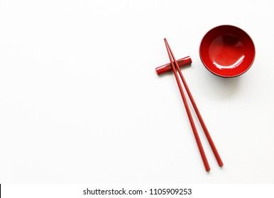Red wood Chopsticks and Red bowl for sushi on White background Copy space