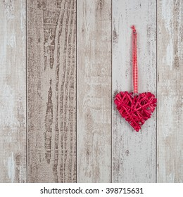 Red wood heart hanging on rustic wooden background