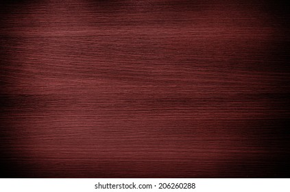 Red wood texture background. Shadow and vignette effect.