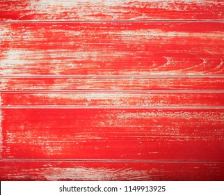 Red wood texture with paint fading and peeling revealing the grain pattern in white