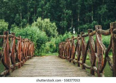 Red wooden bridge on fishing lake with green reeds