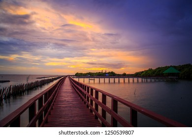 Red wooden bridge out to sea for sunset walk - Shutterstock ID 1250539807