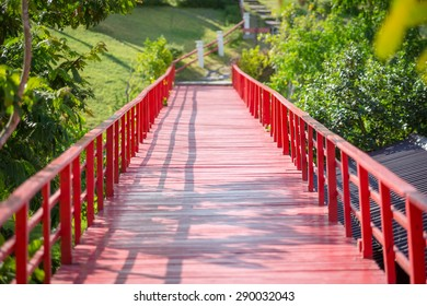 Red wooden bridge over the river in the park.