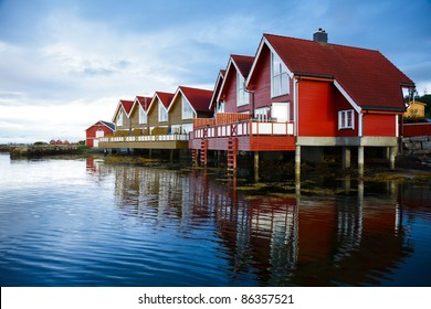 Red wooden cabins at campsite by the fjord in Molde, Norway