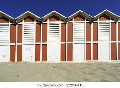 Red wooden cabins on the beach.