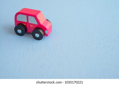 Red wooden car on blue background - Auto insurance concept