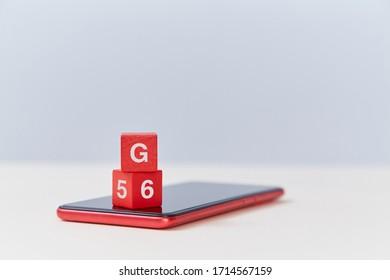 Des cubes rouges en bois avec la lettre G, des numéros sur un smartphone moderne. Génération mobile. Technologie de connexion réseau 5G, 6G
