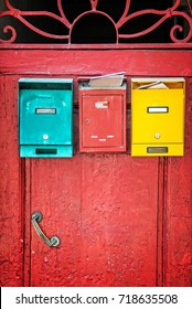 Red wooden door with colorful mailboxes, Florence, Italy