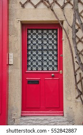 Red wooden door in France with wrought iron decoration