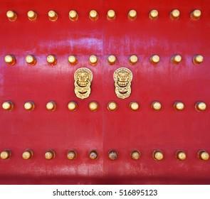 red wooden door or gate and old vintage lion head metal door ring handle knocker