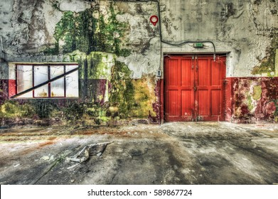 Red wooden door inside a derelict warehouse