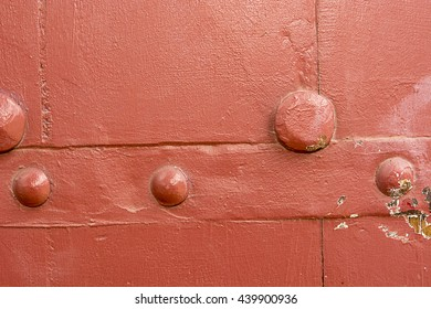 Red wooden door panel with metal stud pattern, The old wood texture with natural patterns