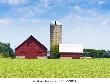 red wooden farm with tall silo