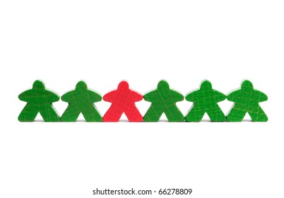 Red wooden figure among green ones symbolizing difference