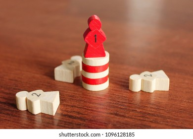 A red wooden figure in the form of a man stands a pedestal of other details. Parts of the board game. Leadership skills. Number one, winner and losers. Back and front background in blur.
