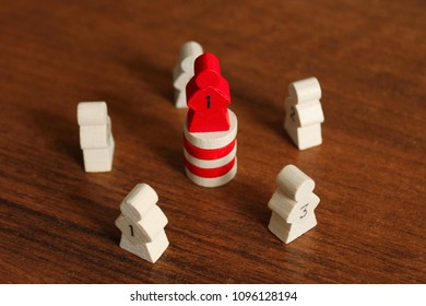 A red wooden figure in the form of a man stands a pedestal of other details. Parts of the board game. Leadership skills. Number one, competition. Back and front background in blur.
