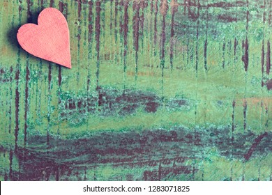 A red wooden heart in front of a green wood background