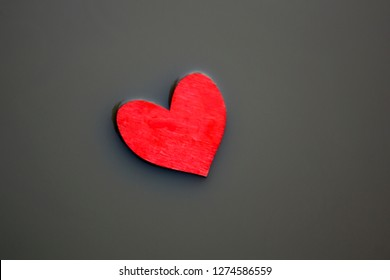 Red wooden heart in a grey muddy slough.