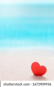 Red wooden heart model on the sandy sea beach with blue sea blurred background, vertical view.