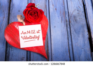 red wooden heart with old blue wooden table top and german text am 14.02. ist valentinstag who means on 14. February is Valentine's Day