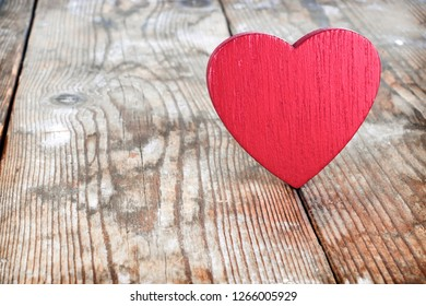 red wooden heart on the background of old boards