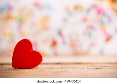 Red wooden heart on a wooden background with boke background.