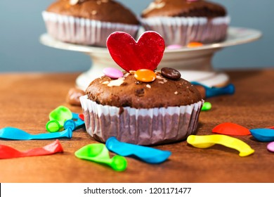 red wooden heart on birthday party chocolate arabic homemade cupcake, madeleine with colorful ballons and smarties