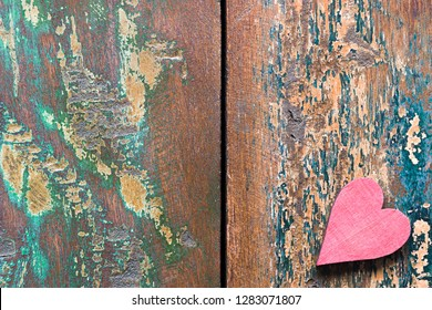 A red wooden heart on a colorful old tabletop