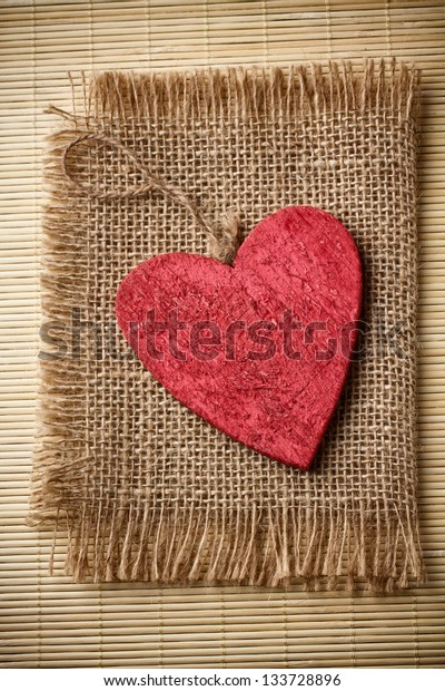 Red wooden heart on a linen cloth and wood background.
