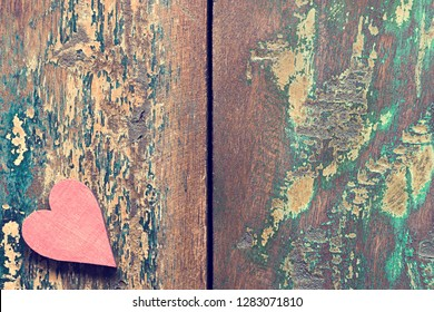 A red wooden heart on an old vintage table