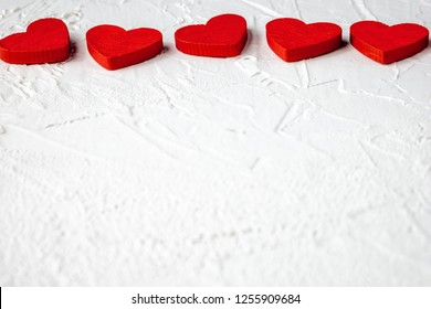 Red wooden hearts in horizontal line on white textured background with copy space. Symbol of love and Valentine's day