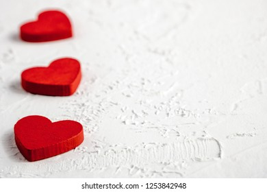 Red wooden hearts in line on white textured background with copy space. Symbol of love and Valentine's day