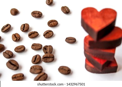 Red wooden hearts on each other and roasted coffee beans spread on white background.
