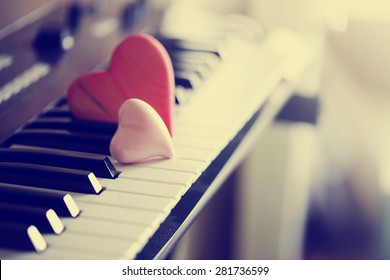 Red wooden hearts on a piano keyboard/ selective focus