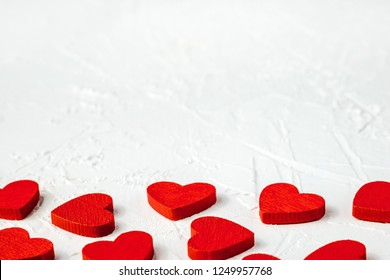 Red wooden hearts on white textured background with copy space. Symbol of love and Valentine's day