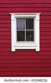 Red wooden house facade with window