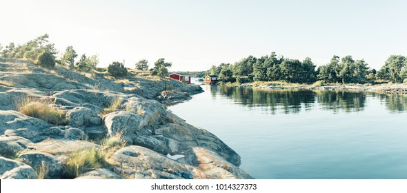 Red wooden house in lake landscape in Sweden, forest, panorama in summer, Norrmalm, Sundsvall, Gothenburg, Gotland
