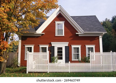 Red wooden house with white picket fence in autumn, New England