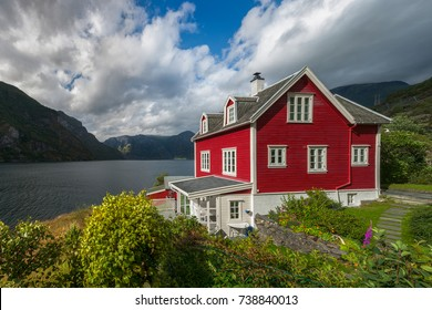 Red wooden house with white trimmings in green garden with lake, mountains and blue sky with white clouds in background, Norway