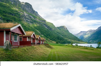 Red wooden houses with grass on it's roofs. Norwegian camping near the popular touristic attraction - Briksdalsbreen glacier, Norway.