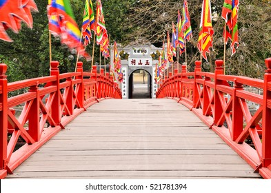 Red wooden Huc Bridge from the Ngoc Son Temple in Hanoi Vietnam leading to the exit door. Left and right waving flags in the wind