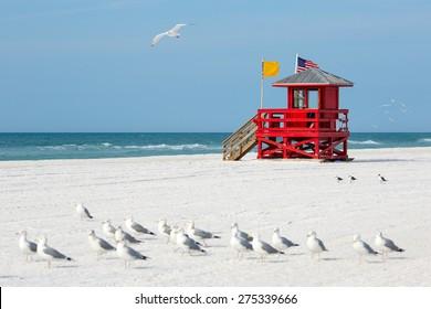 Red wooden lifeguard hut on an empty morning beach