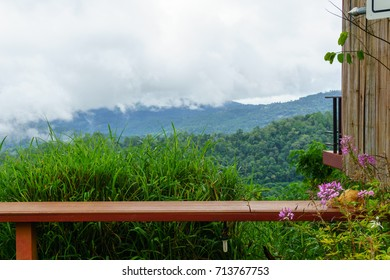red wooden long chair with panorama view of mist in the valley