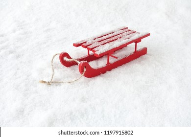 Red wooden sledge with rope in snow covered with snowflakes.