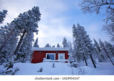 Red wooden Swedish house in winter forest covered with snow, Kurravaara, Sweden