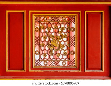 Red wooden wall with beautiful carved window at the Purple Forbidden City in the Imperial City within the Citadel in Hue, Vietnam. Hue is a popular tourist destination of Asia.