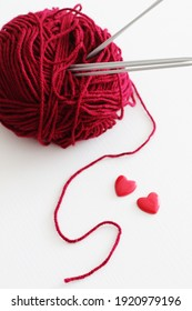 red wool ball with hearts and knitting needles